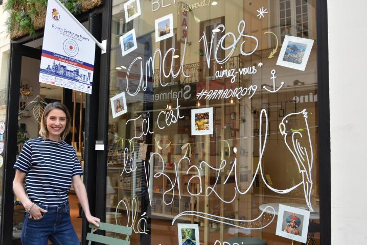 La responsable d'Amaï devant la vitrine du magasin qui est décorée dans le thème du Brésil