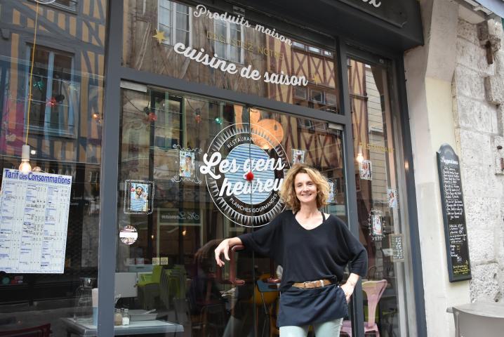 La restauratrice des Gens Heureux pose devant la devanture de son restaurant