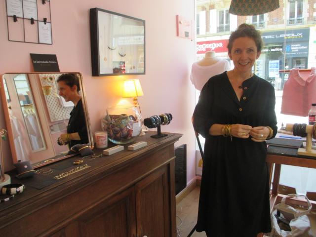 Mademoiselle Gridou pose dans la boutique devant un meuble où se trouvent exposés les bijoux