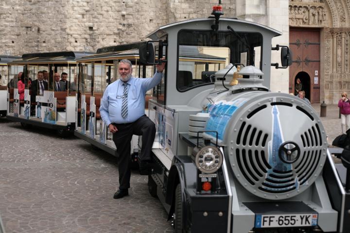 Le train gris clair, avec sa locomotive et ses trois wagons devant la cathédrale de Rouen
