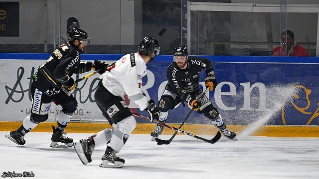 Deux joueurs de hockey en noir de Rouen jouent face à un joueur en blanc de Chamonix sur la glace de Rouen