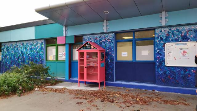 La boîte à dons couleur framboise devant le mur bleu du centre socio-culturel Simone-Veil