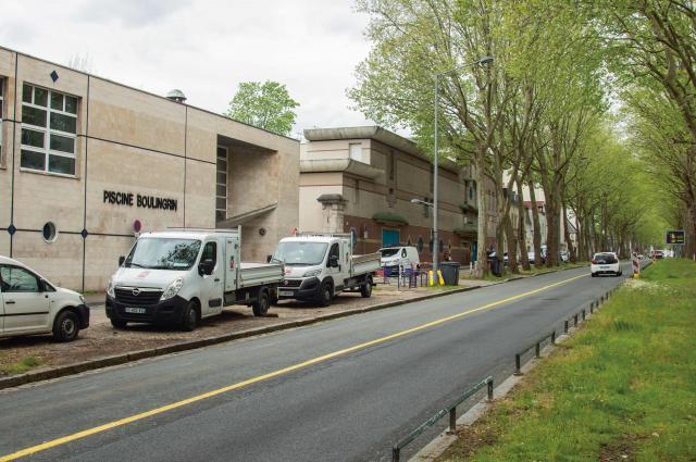 Photo de la piscine Boulingrin vue du boulevard de Verdun avec sa façade beige et devant des camionnettes blanches qui stationnent sur le trottoir