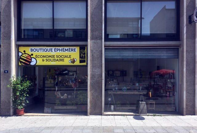 """Vitrien vue de la rue Jeanne d'Arc de la boutique éphémère avec vitrines vitrées et un bandeau jaune au-dessus de la porte avec l'inscription """"Boutique éphémère économie sociale et solidaire"""""""