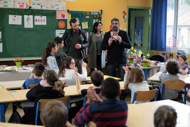 Frédéric Marchand, livre à la main, devant les enfants de l'école Jules-Ferry de Rouen