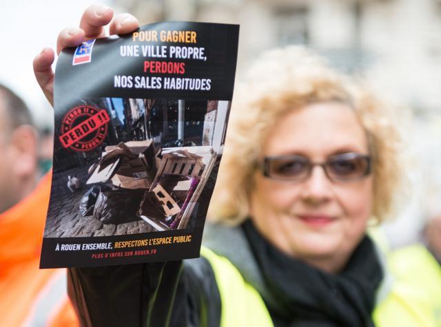 Femme tendant un flyer Pour gagner une ville propre, perdons nos sales habitudes