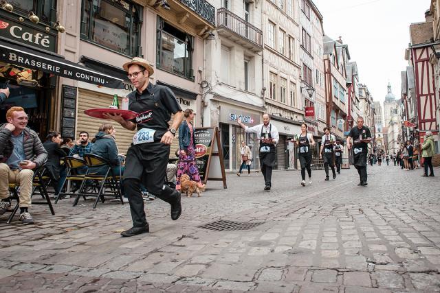 Des garçons de café courent rue du Gros-Horloge © Barbara Cabot