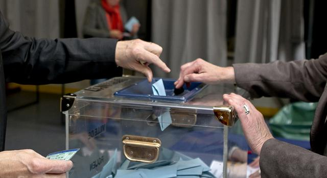 Main qui dépose un bulletin de vote dans une urne