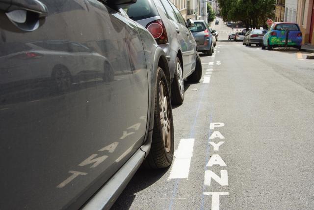 Inscription payant au sol avec reflet dans une voiture