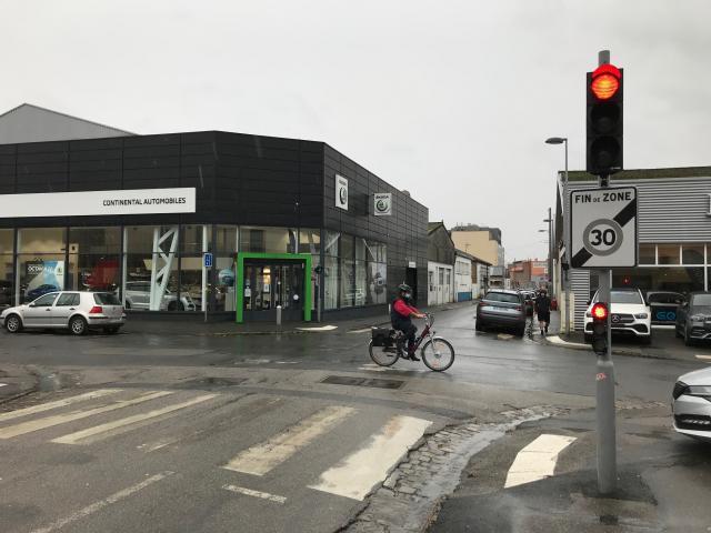 Le feu de la rue Jean-Ango et une cycliste au milieu du carrefour