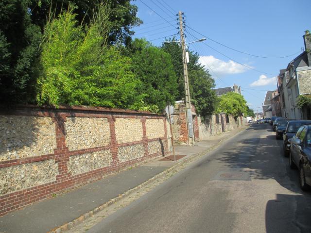 Vue de la voirie de la rue Chasselièvre avec à gauche un mur de jardin en briques rouges et beiges et à droite, des voitures en stationnement sous un ciel bleu  e