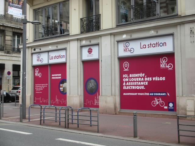 """Vue du trottoir d'en face de la façade de la vélo station rue Jeanne d'Arc avec une vitrine dotée d'affiches roses plastifiées sur lesquelles est écrit """"ici, bientôt, on louera des vélos électriques"""""""