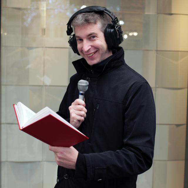 Matthieu Farcy, casque sur les oreilles, micro et livre à la main