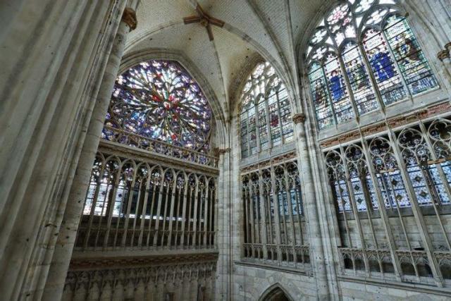 Vue à hauteur de vitraux de la rose du transept sud de l'abbatiale Saint-Ouen, de l'intérieur de l'édifice avec des vitraux de couleurs rouge et bleu