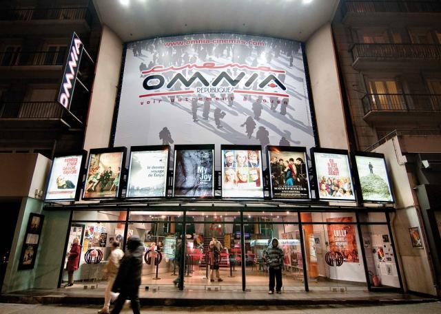 Façade éclairée du cinéma Omnia de nuit avec l'écran des affiches éclairé