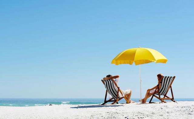 Deux personnes sur la plage sous un parasol