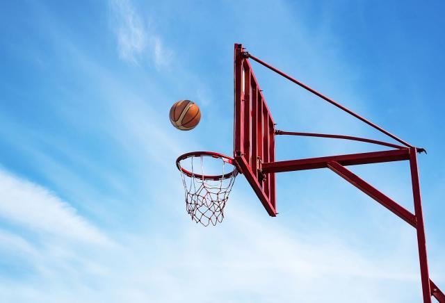 Panier de basket extérieur avec structure peinte en rouge, filet blanc sur fond de ciel bleu