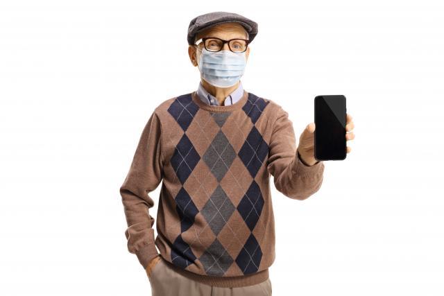 Senior avec son téléphone portable et un masque