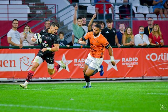 Paré de la tunique noire des Lions, l'ailier du Rouen Normandie Rugby Paul Surano, ballon en main, s'apprête à inscrire l'un de ses deux essais contre Narbonne