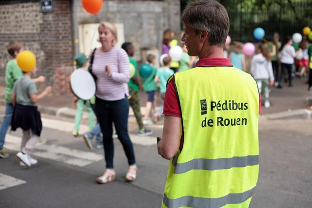 Accompagnateur Pédibus et des enfants sur un passage protégé