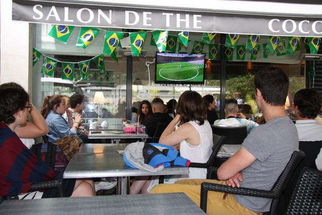 Des personnes installées en terrasse d'un restaurant avec un match sur l'écran