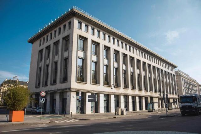 Vue du quai de la Bourse et de sa voirire sans voiture ni piéton, sur laquelle figure le Palais des consuls, bâtiment beige à colonnes vue de profil