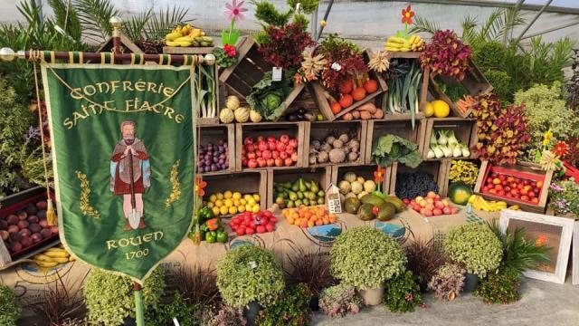 Le blason de la Confrérie Saint-Fiacre de Rouen trône devant un décor multicolore de fruits et légumes frais