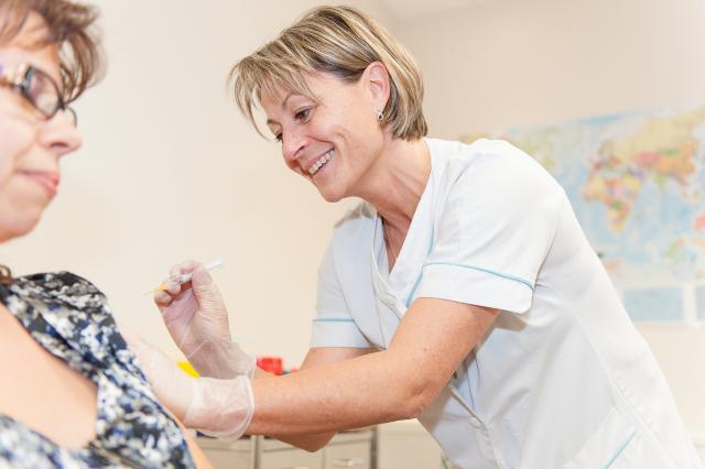 Une femme se fait vacciner par une infirmière